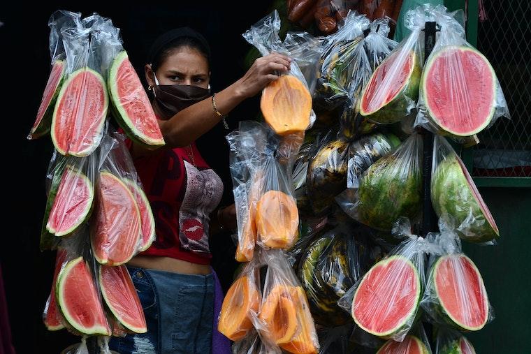 A fruit vendor standing next to bags of sliced fruit
