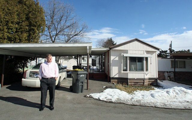 A man stands in front of his car and mobile home.
