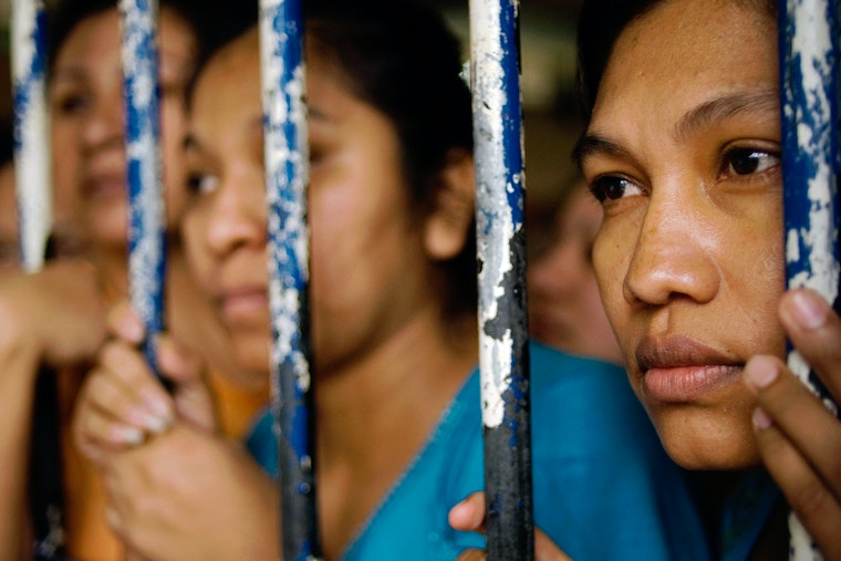 Women behind bars in a jail cell
