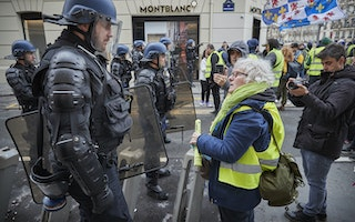 Demonstrator facing a riot police officer