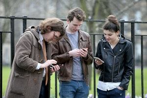 three people looking at their phones