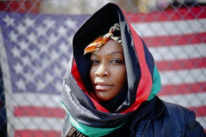 A woman in a scarf in front of an American flag