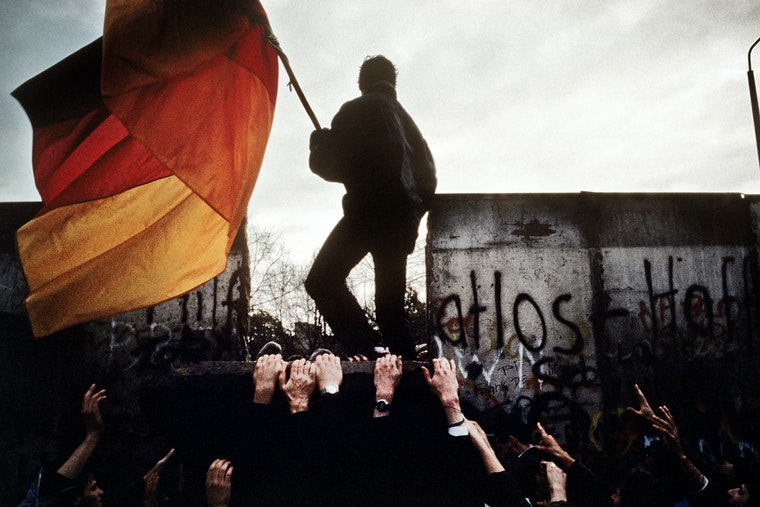 A man standing on top of a section of wall waving a large German flag.