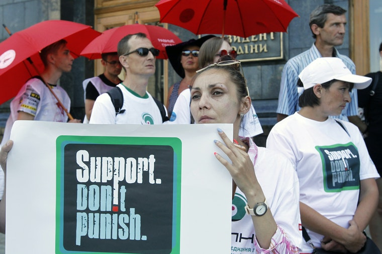 People wearing T-shirts and holding signs that state 'Support. Don't Punish'