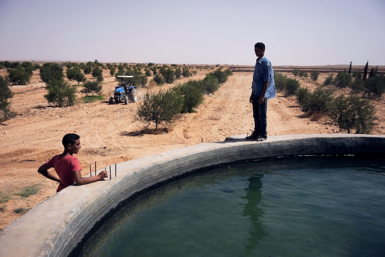 A man stands next to a water tank used to irrigate crops.