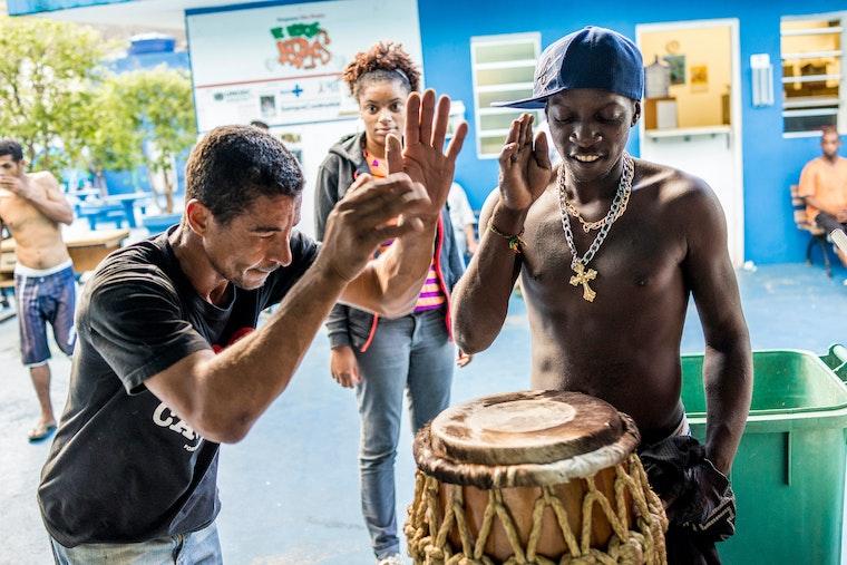 Two men in São Paulo, Brazil play drums.