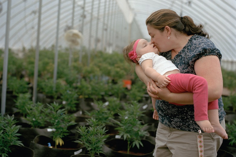 A woman holding her toddler in a greenhouse