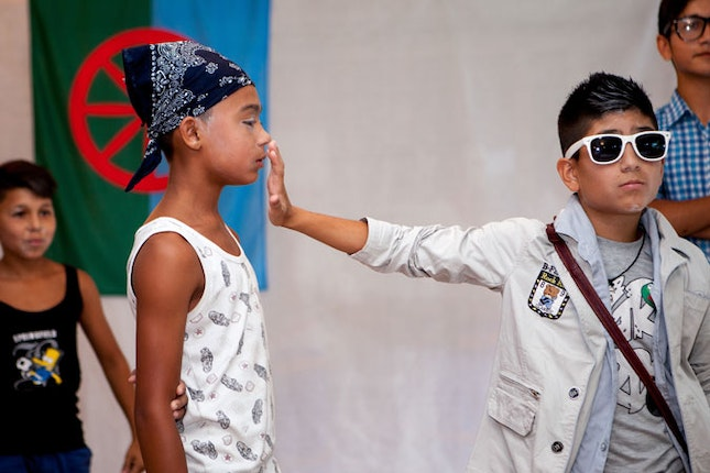 Boy wearing sunglasses holds his hand out to another boy's face.