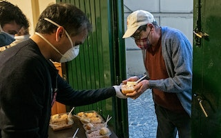 A man accepts food from a soup kitchen