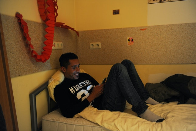 Man on a smart phone reclining on a bed