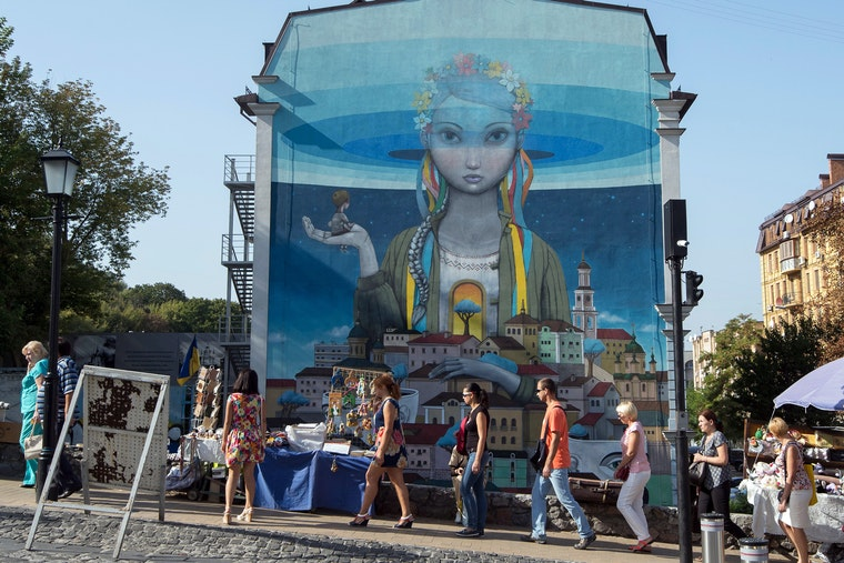People walking past a mural