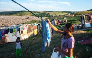 A young woman hangs laundry next to a landfill