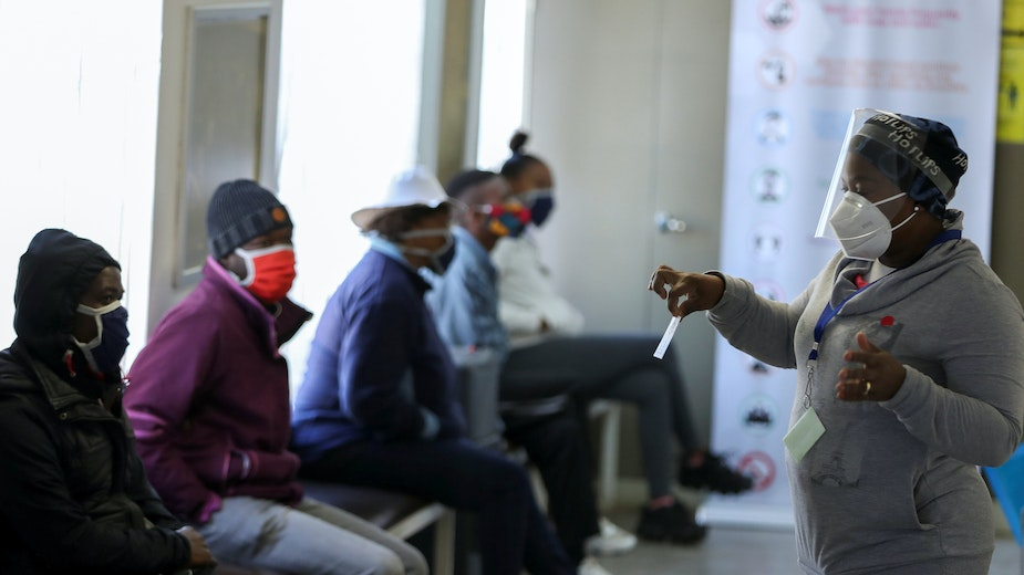 A medical worker speaks to volunteers as they wait to receive a potential COVID-19 vaccine during clinical trials in Soweto, South Africa, on June 24, 2020.