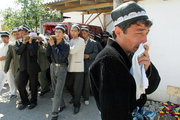 Casket attended by mourners