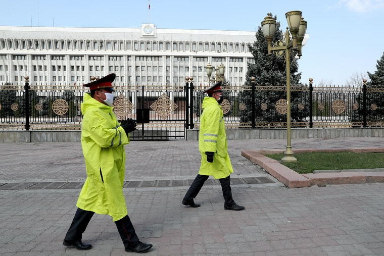 Two police officers in face masks walk in front of an ornate fence surrounding a government building