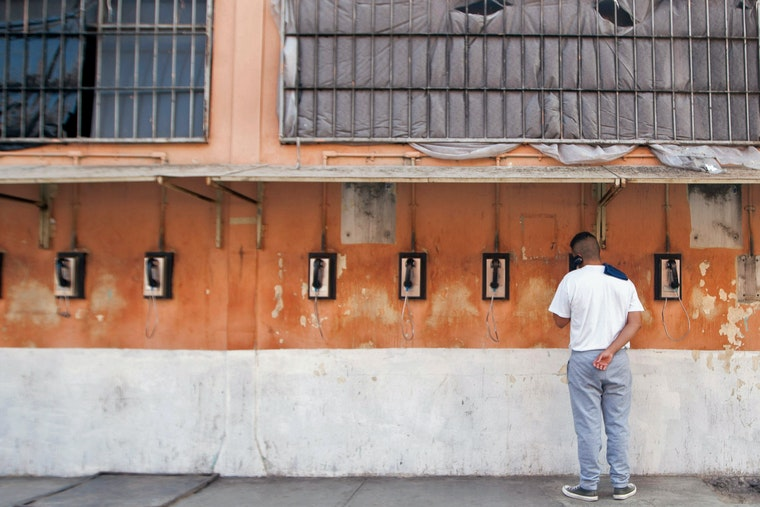 An inmate speaks on the phone against the wall