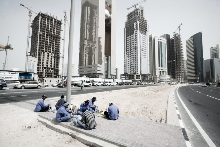 A group of workers sit on the pavement during their lunch break.