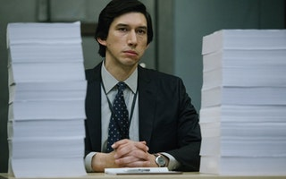 Adam Driver sitting with large stacks of paper in front of him