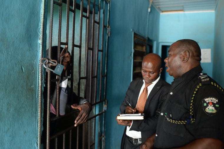 A policeman speaks to a prisoner who is behind bars while the prisoner's lawyer takes notes on a legal pad.