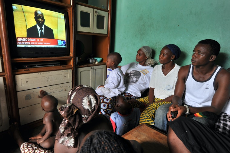 A family gathered around a television, watching a politician deliver a speech before a tribunal.