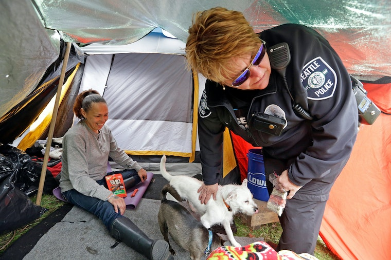 A police officer smiles inside of a tent while greeting a woman and giving a treat to her pet dog.