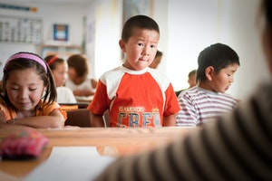 A child standing at a desk in a classroom