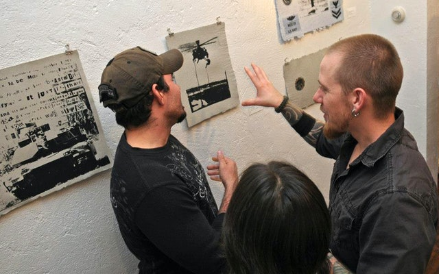 People looking at artwork on a wall.