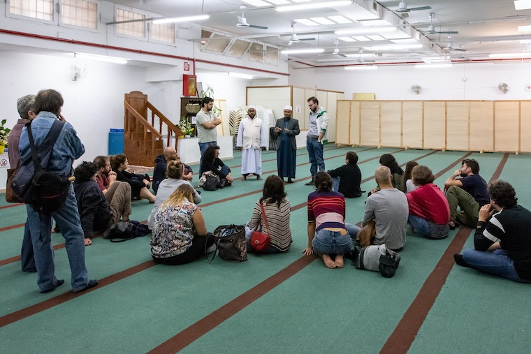 A group of people sits on the floor of a mosque