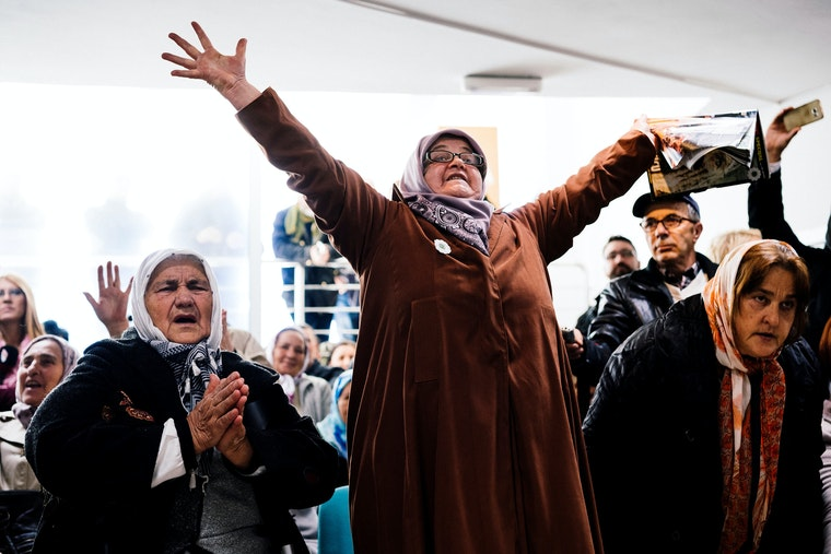 A group of people who are watching a UN court deliver its ruling on TV celebrate by either holding their arms aloft or putting their hands together in prayer.