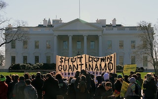 "A large banner in front of the White House that says ""Shut Down Guantanamo"""