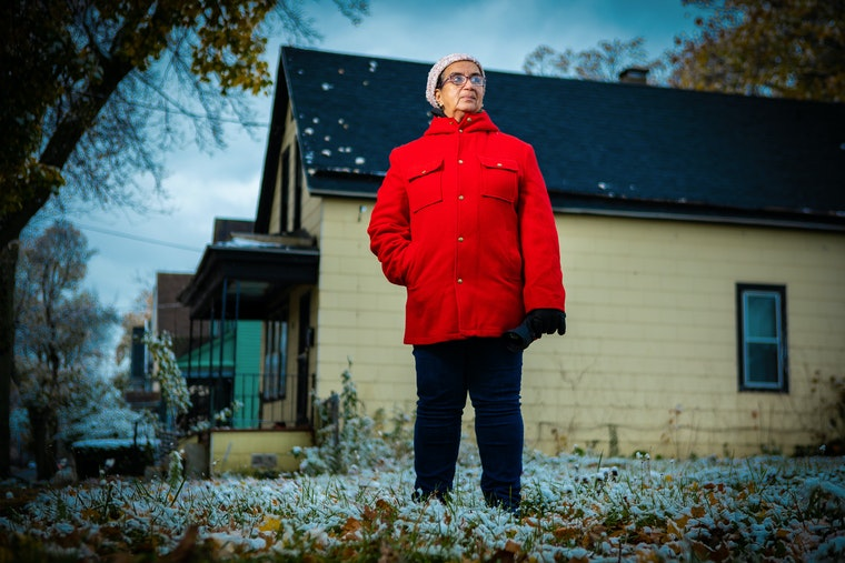 Dennice Barr in a red coat standing outside her home