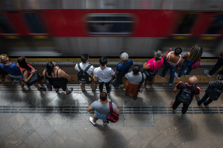 People seen from above standing near a train