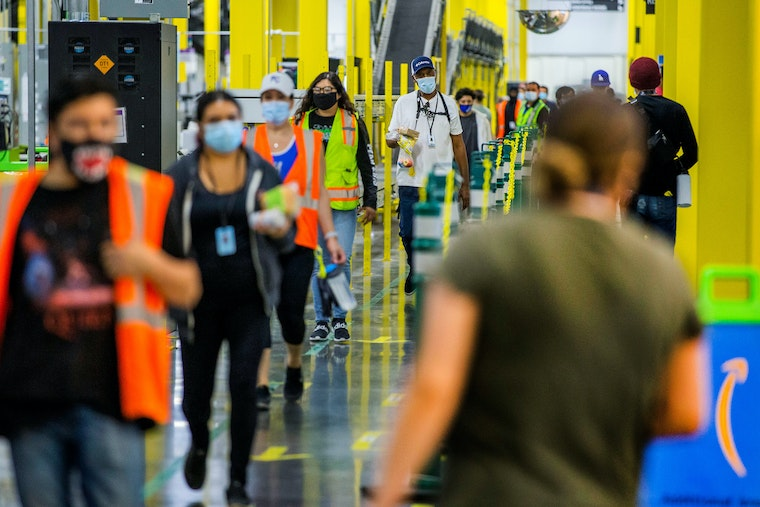People wearing vests and masks walk in a line at a warehouse
