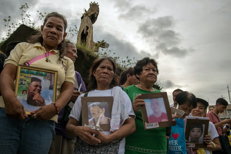 A group of people standing in mourning