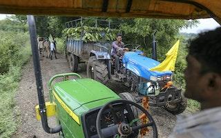 Men driving tractors on a dirt road