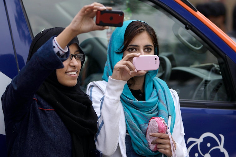 Two women hold up their mobile phones to record a protest in Islamabad, Pakistan.