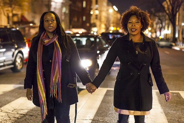 Women hold hands outside