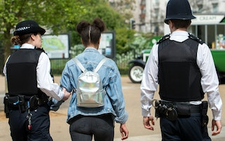 Two police officers arresting a woman