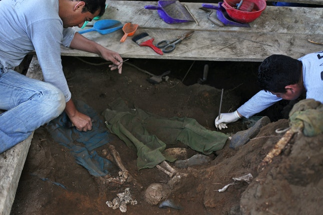 Two people clearing dirt from skeletal remains