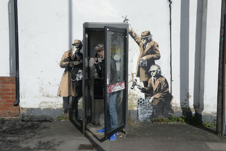 A man stands in a telephone booth which is next to a wall that has been painted by a street artist so as to look like it is surrounded by men wearing trench coats and sunglasses and operating surveillance equipment.