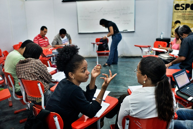 Young adults, students, sit in their desks, which are arranged in a half-circle and facing the whiteboard.