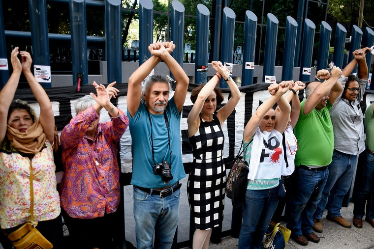 A line of people with their arms in the air and their wrists crossed as if their hands were bound.