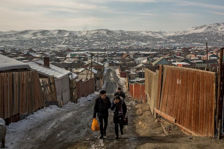 People walk up an unpaved street in a residential neighborhood