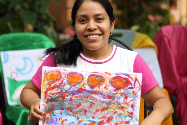 A woman smiles while holding up a piece of artwork