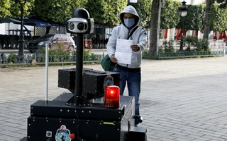 A man holds up a piece of paper to a police robot on a public sidewalk