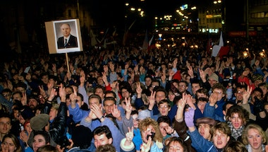 A large crowd at a demonstration in a street at night