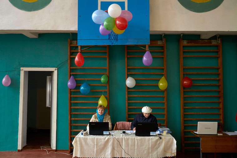 Two women sit in front of computers in a gymnasium which is decorated with balloons.