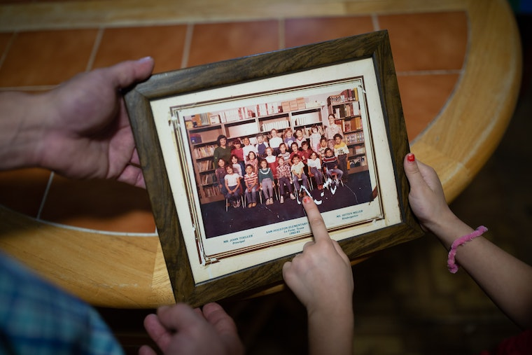 A finger pointing to a framed class photo