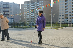 A woman walking with the help of a cane