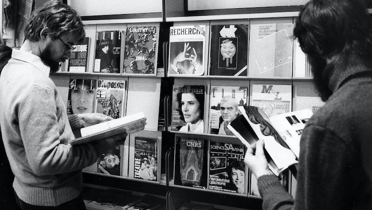 People browsing magazines in front of a rack of periodicals